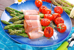 Green asparagus with ham and grilled cherry tomato Stock Image