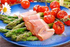 Green asparagus with ham and grilled cherry tomato Stock Photo