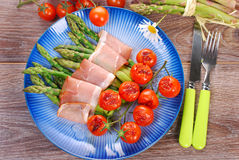 Green asparagus with ham and grilled cherry tomato Royalty Free Stock Images