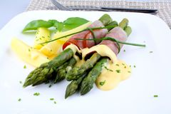 Green asparagus with ham and sauce, close up Stock Image
