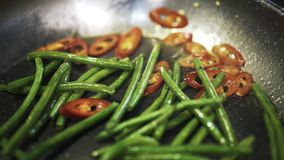 Green asparagus and hot pepper fried and stirred stock video