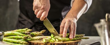 Green asparagus kept in men`s Chef cook hands royalty free stock photo