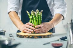 Green asparagus kept in men`s Chef cook hands stock image