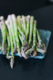Green asparagus on marble cutting board. Dark background stock photos