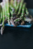 Green asparagus on marble cutting board. Dark background stock photography