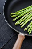 Green asparagus in the pan. Black background, top view, space for text. royalty free stock photography