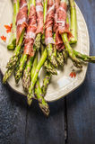 Green asparagus with parma ham in plate on rustic blue wooden background Royalty Free Stock Photo