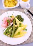 Green asparagus with potato, prosciutto and sauce stock image