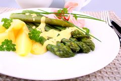 Green asparagus with prosciutto, potato, chives and sauce Royalty Free Stock Photos