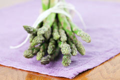 Green asparagus on purple napkin Stock Images