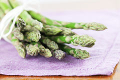 Green asparagus on purple napkin Stock Photos