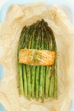 Green asparagus with salmon. Baked green asparagus with salmon with parchment paper in a casserole Stock Image