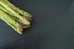 Green asparagus on slate platter. Fresh green asparagus from market on a black slate platter Stock Image