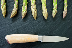 Green asparagus on slate platter. Green fresh asparagus spears with a knife on a black slate platter Royalty Free Stock Images
