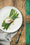 Green asparagus with soft-boiled egg. Healthy breakfast. Flat-lay of green asparagus with soft-boiled egg, leek and bacon served in white plate over rustic Stock Photography