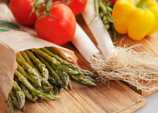 Green  asparagus. And tomatoes on a wooden table Royalty Free Stock Photography