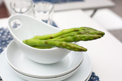 Green asparagus in white bowl. Green asparagus in bowl, summer garden decoration Stock Photos