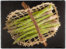 Green asparagus in wicker basket Stock Images