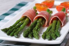 Green asparagus wrapped in ham close up horizontal Stock Images