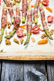 Green Asparagus wrapped in Parma ham with tomatoes, parmesan, Walnut  and dried apricot , ready for cooking Stock Photography