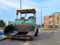Green asphalt spreader machine at the site of road construction in the city. Front view, summer day royalty free stock photography