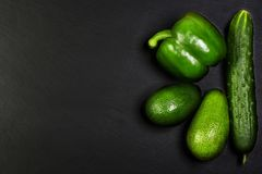 Green assortment vegetables, avocados, pepper and cucumber on a shale board, the concept of healthy eating, copy space, top view s. Et Royalty Free Stock Photo