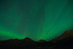 Green Aurora. Lights up the night sky over mountains Stock Photography