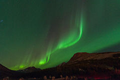 Green Aurora. Lights up the night over mountains Royalty Free Stock Images