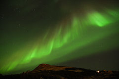 Green Aurora. Lights up the night over mountains Stock Photo