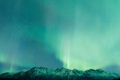 Green Aurora Over Mountains. Green Aurora lights up the sky and mountains Royalty Free Stock Photos