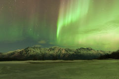 Northern Lights Over Mountains. Green Aurora lights up the sky and mountains Royalty Free Stock Photography