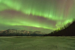 Green Aurora Over Mountains And A Frozen Lake. Green Aurora lights up the sky and mountains Stock Images