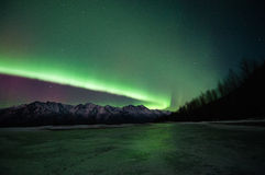 Green Aurora Over Mountains And A Frozen Lake. Green Aurora lights up the sky, mountains and a frozen lake Royalty Free Stock Images