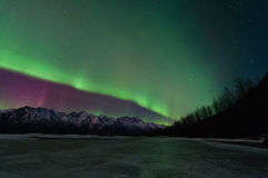 Green Aurora Over Mountains And A Frozen Lake. Green Aurora lights up the sky, mountains and a frozen lake Stock Image
