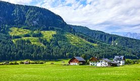 Green Austrian village in Alps. Traditional village among Austrian meadows, fields and Alpine mountains. Knolls covered with green forests and blue sky with Stock Photography