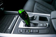 Green Automatic gear stick transmission of a modern car, multimedia and navigation control buttons. Car interior details. royalty free stock photography