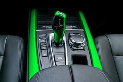 Green Automatic gear stick transmission of a modern car, multimedia and navigation control buttons. Car interior details. Transm stock photos