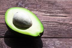 Green avocado cut into halves on a wooden table with a shallow depth of field stock image