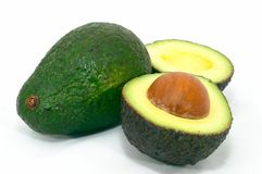 Green Avocado with cut ripe Stock Images