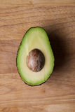 Half and avocado on wooden chopping board Stock Photos