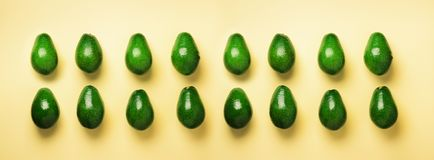 Green avocado pattern on yellow background. Banner. Top view. Pop art design, creative summer food concept. Organic avocadoes in m. Inimal flat lay style royalty free stock photo