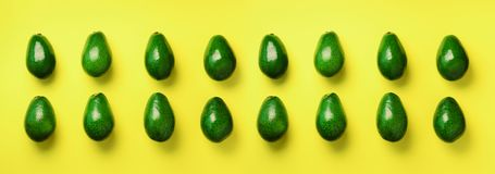 Green avocado pattern on yellow background. Top view. Pop art design, creative summer food concept. Organic avocadoes in. Minimal flat lay style stock image