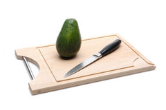 Green avocado on wooden board isolated on white Royalty Free Stock Image