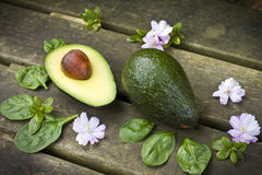 Green avocados and spinach. On the wooden table with spring flowers Royalty Free Stock Image
