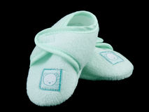 Green baby booties on black. Closeup picture of little soft shoes for newborn baby, on black background Stock Images