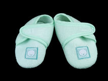 Green baby booties on black. Closeup picture of little soft shoes for newborn baby, on black background Stock Photo