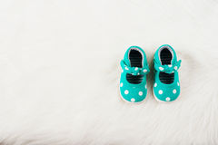 Green baby girl shoes with white dots. On a white fur carpet. Stock Photo