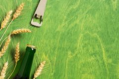 Green background with beer bottle, opener and ears of wheat stock image