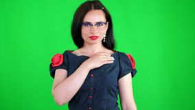 Green background, chroma key. Portrait of a sexy brunette woman with red lips, in stylish glasses, spectacles, eroticly. Playfully moves, looking sexually at stock video footage