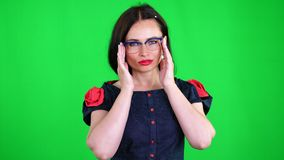 Green background, chromeakey. portrait of a sexy brunette woman with red lips, in stylish glasses, spectacles, eroticly. Playfully moves, looking sexually at stock video footage